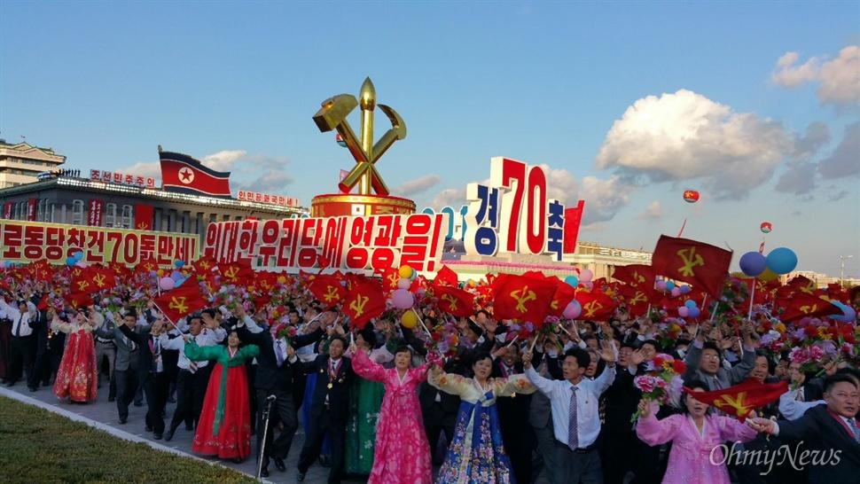 조선노동당 창건 70년 기념 열병식 현장. '위대한 우리 당에 영광을'이라는 문구 아래 북한 인민들이 손에 꽃을 들고 행진하고 있다.