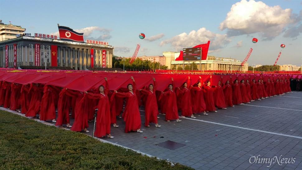 조선노동당 창건 70년 기념 열병식 현장. 북한 예술인들이 붉은 천 등을 이용해 조선노동당기를 형상하면서 행진하는 모습.