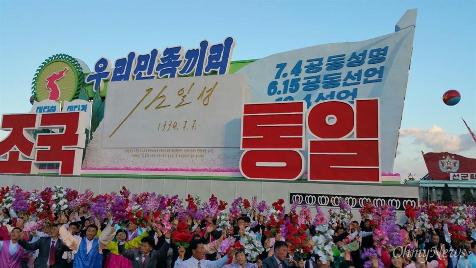 조선노동당 창건 70년 기념 열병식 현장. '우리민족끼리 조국통일'이라는 문구가 적혀 있는 구조물 아래서 열병식에 참석한 관중들이 꽃을 든 채 두 팔을 들어올리고 있다.