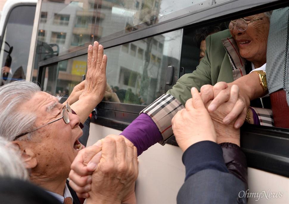 22일 강원도 고성 금강산 이산가족면회소에서 열린 제20차 남북이산가족상봉 작별상봉을 마친후 북측 가족들이 버스에 탑승한 가운데 남측 가족들이 손을 잡으며 눈물로 배웅하고 있다.