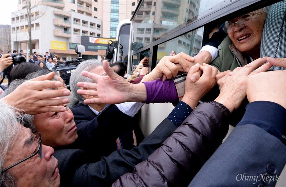 22일 강원도 고성 금강산 이산가족면회소에서 열린 제20차 남북이산가족상봉 작별상봉을 마친후 북측 가족들이 버스에 탑승한 가운데 남측 가족들이 마지막으로 손을 잡으며 눈물로 배웅하고 있다.