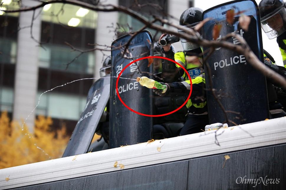 '1등 식용유'가 경찰 진압장비(?) 민중총궐기 대회가 열린 14일 오후 서울 청계광장에 설치된 경찰차벽 위에서 한 경찰관이 식용유를 집회 참가자들에게 뿌리고 있다. 경찰이 들고 있는 플라스틱병 표면에 '1등 식용유'라는 문구가 선명하게 보인다. 경찰은 이날 집회참가자들이 버스에 올라오지 못하게 하기 위해 식용유를 버스 표면에 뿌리기도 했다.