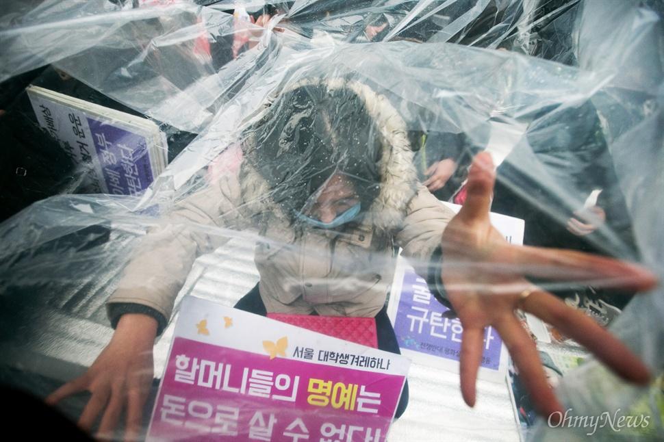 30일 오후 서울 종로구 일본대사관 앞에서 평화나비 네트워크 등 대학생들이 비를 맞으며 평화의 소녀상 비를 맞으며 주변 자리를 지키고 있다.