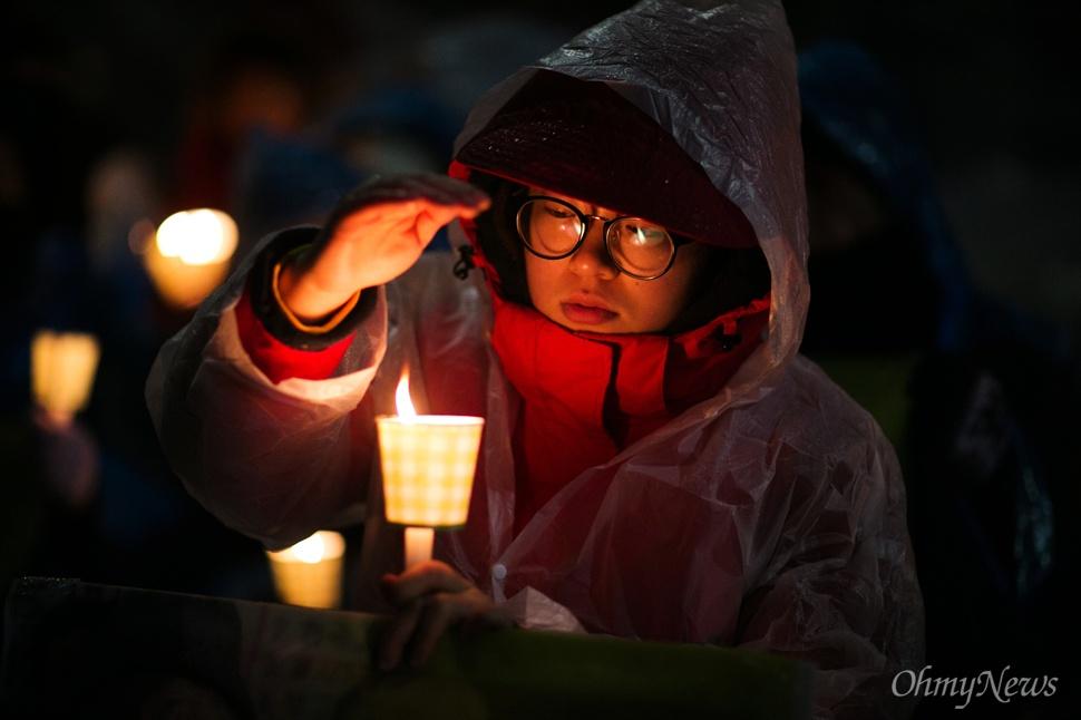 '촛불 꺼지면 안되요' 30일 오후 서울 종로구 일본대사관 앞에서 평화나비 네트워크 등 대학생들이 비를 맞으며 평화의 소녀상 주변 자리를 지키고 있다.