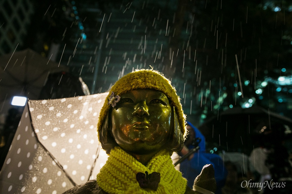 30일 오후 서울 종로구 일본대사관 앞 평화의 소녀상 위로 비가 내리고 있다.