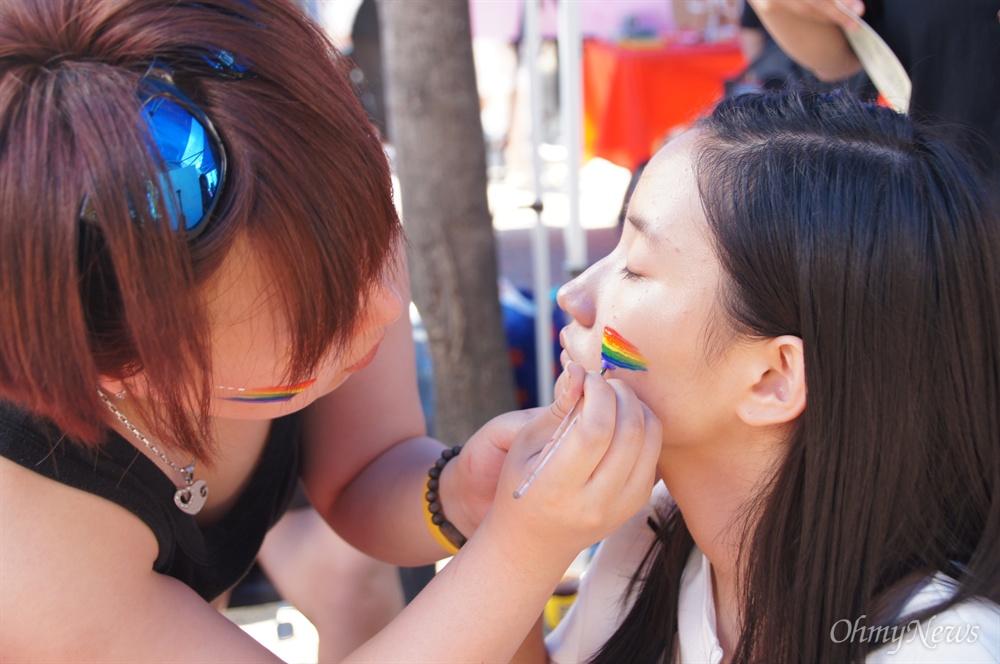 26일 오후 대구에서 열린 퀴어축제에 참가한 한 참가자가 얼굴에 퀴어를 뜻하는 무지개 모양의 페이스페인팅을 하고 있다.