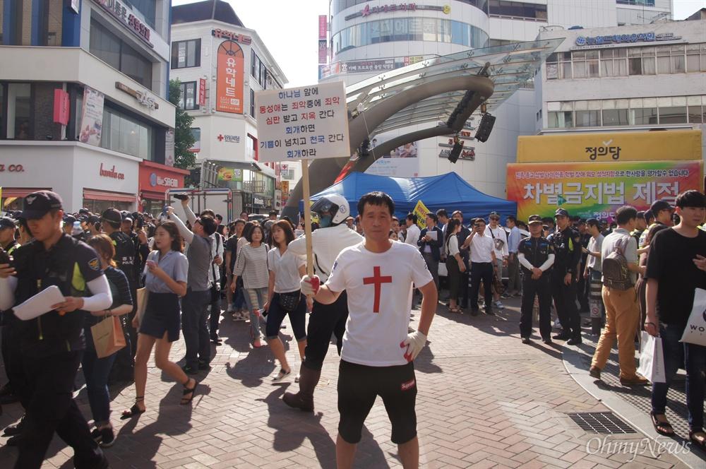26일 오후 대구에서 열린 퀴어축제 참가자들이 퍼레이드에 나서려 하자 한 기독교단체 회원이 피켓을 들고 행진을 막기 위해 서 있다.