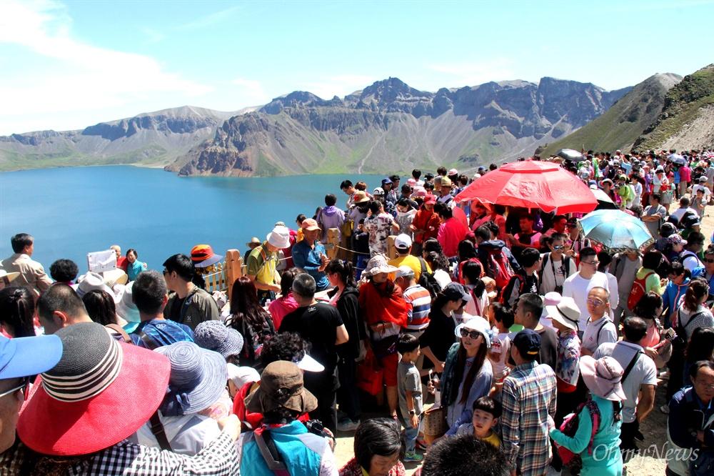8월 9일 백두산 서쪽 정상에 많은 사람들이 모여 구름 한 점 없는 가운데 드러난 천지를 감상하고 있다.