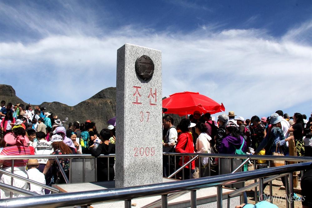 8월 9일 백두산 서쪽 정상에 있는 북한(조선)-중국 경계비 주변에 많은 사람들이 있다.