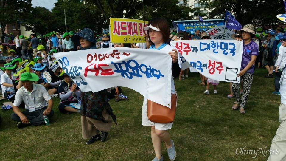 사드 배치 철회를 요구하는 성주군민들의 삭발식이 진행된 15일 오후 결의대회에 참석한 주민들이 직접 손으로 쓴 현수막을 들고 무대 앞으로 걸어나오고 있다.