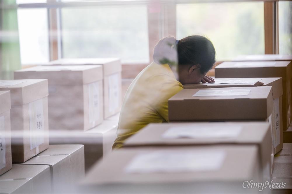 20일 오후 경기도 안산 단원고등학교에서 희생학생들의 유품과 책상을 안산교육지원청 별관으로 이전을 위한 작업이 진행 되기 전 한 세월호 유가족이 유류품 상자에 엎드려 눈을 감고 있다.