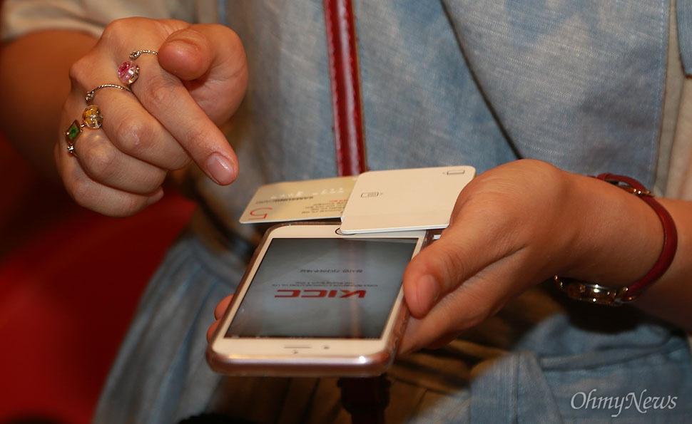 12일 오후 서울 여의도 한강공원에서 열린 '서울밤도깨비야시장'에서 판매자가 스마트폰 단말기를 이용해 소액 요금까지 즉석에서 신용카드로 결제를 해주고 있다.