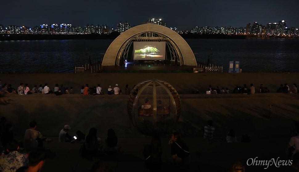 시민들이 12일 오후 서울 여의도 한강공원에서 열린 '서울밤도깨비야시장'을 찾아 무더위를 식히며 영화를 관람하고 있다.
