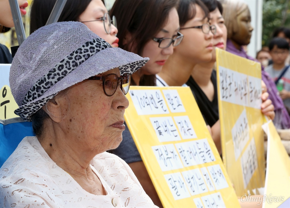 """추석 연휴에도 변함없이, 김복동 할머니... 추석 연휴 첫날인 14일 서울 중학동 옛 일본대사관 맞은편에서 열린 1248번째 수요시위에 일본군 위안부 피해자인 김복동 할머니가 참여하고 있다. 할머니의 오른편에 """"10억엔을 받고 끝내는 것은 정부가 할머니들을 팔아넘기는 것 밖에 안된다""""고 적힌 노란 피켓이 보인다."""