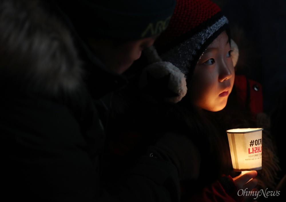 박근혜 퇴진 광화문광장은 산 교육장  26일 오후 서울 광화문광장에서 열린 박근혜 퇴진 5차 범국민행동에서 촛불을 든 한 어린이가 연설과 공연을 지켜보고 있다.