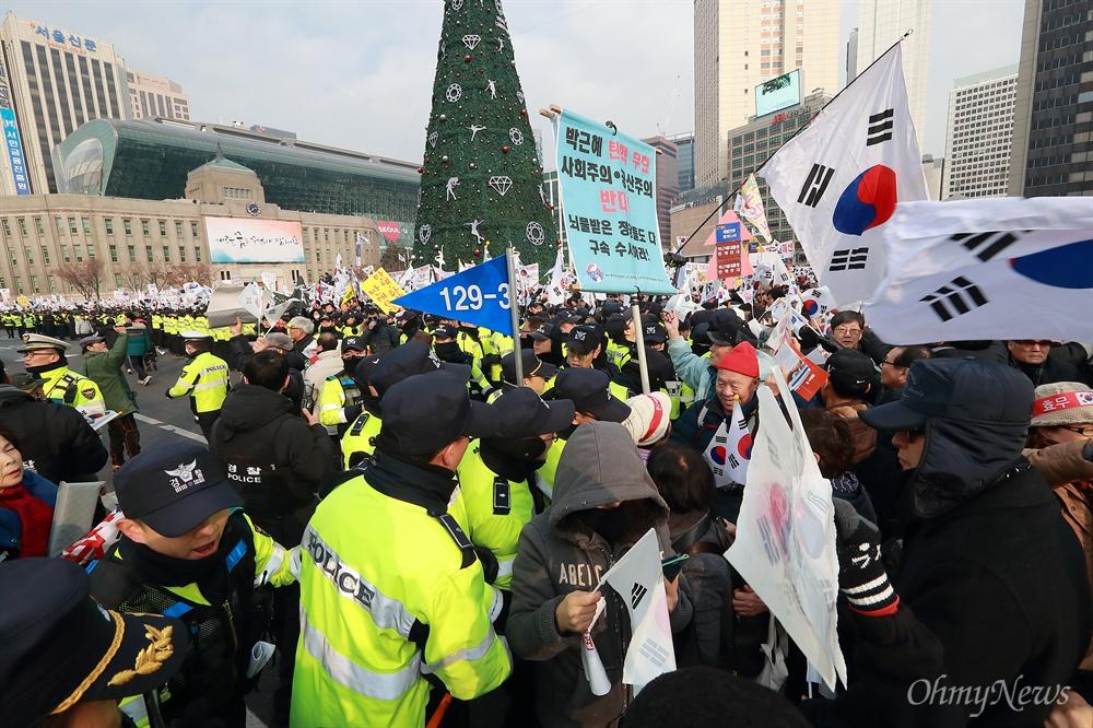 폴리스라인 밀어내고 도로 점거하는 박근혜 지지자들 31일 오후 서울 덕수궁 대한문앞에서 박사모 등 박근혜 대통령 지지자들이 모인 탄기국(대통령탄핵기각을 위한 국민총궐기운동본부) 주최로 탄핵 반대 집회가 열리고 있다. 집회 참가자들이 공간을 부족하다며 경찰을 밀어내고 도로를 점거하고 있다.