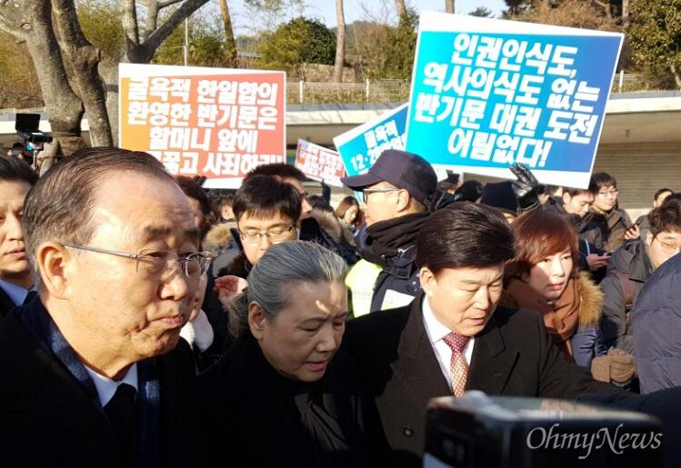 반기문 전 유엔사무총장이 17일 오전 고 노무현 전 대통령 묘소를 참배하기 위해 차량에서 내려 이동하자 시민이 항의하는 내용의 손팻말을 들고 서 있다.