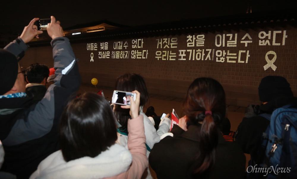 광화문 담벼락에 비춰진 세월호참사 진상규명 레이져 불빛 4일 오후 서울 종로구 광화문광장에서 열린 '2월에는 탄핵하라-14차 범국민행동의 날'에 참석한 시민들이 광화문 담벼락에 레이저 불빛으로 '어둠은 빛을 이길 수 없다. 거짓은 참을 이길 수 없다. 진실은 침몰하지 않는다. 우리는 포기하지 않는다'를 만들어보이며 세월호참사 진상규명을 촉구하고 있다.