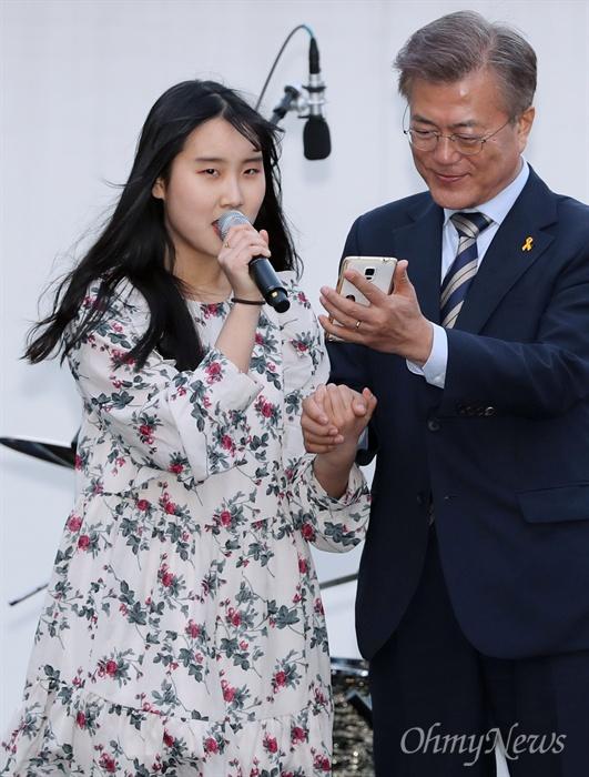 한 손엔 스마트폰, 또 한 손은...  문재인 더불어민주당 대선후보가 사전투표 25퍼센트 프리허그 약속을 지키기 위해 6일 오후 서울 마포구 홍대 앞 걷고싶은거리에서 열린 '투표참여 릴레이 버스킹 vote0509'에 참여했다. 이날 무대에 오른 한 시민이 '마법의 성' 노래를 부르는 동안 가사를 볼 수 있도록 문 후보가 스마트폰을 받쳐 들고 있다.