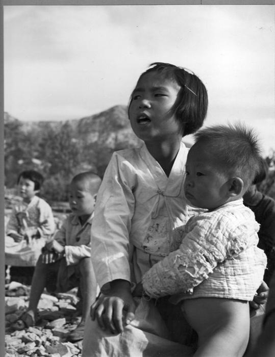 1950.10. 서울 은평. 한 소녀가 동생을 돌보며 불타버린 야외교실에서 수업을 받고 있다.