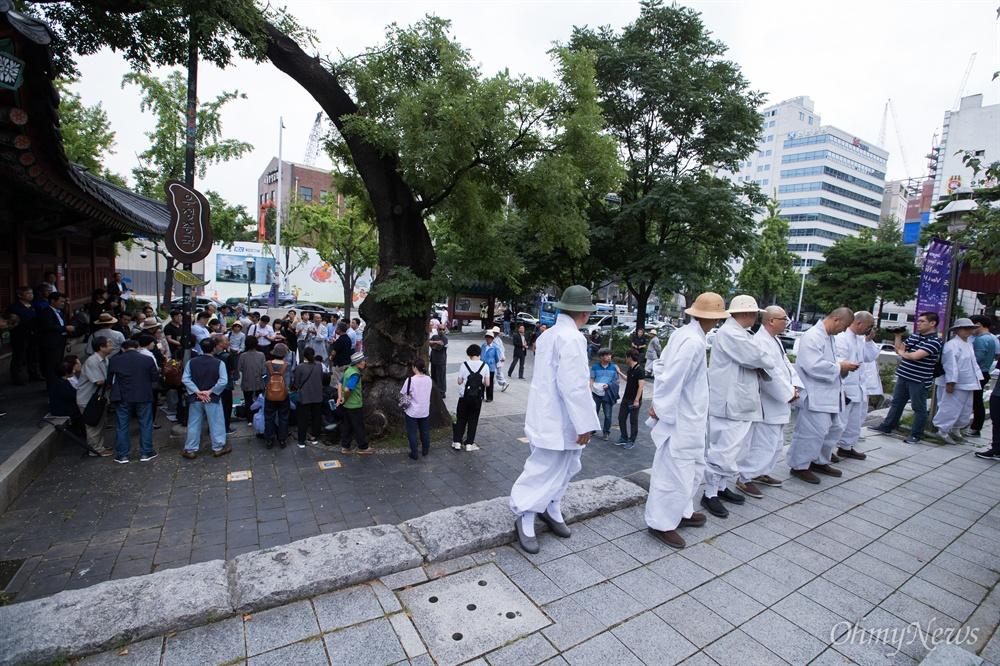 명진스님이 18일 오전 조계사 입구에서 조계사 자승 총무원장 퇴진 촉구 단식 농성을 시작하자 조계사 관계자들이 단체로 지켜보고 있다.
