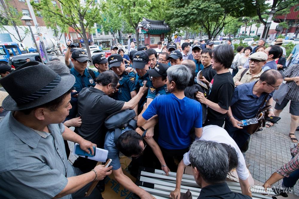 명진스님이 18일 오전 조계사 입구에서 조계사 자승 총무원장 퇴진 촉구 무기한 단식농성을 시작하자 지지자들이 천막을 설치하고 경찰이 막아서고 있다.