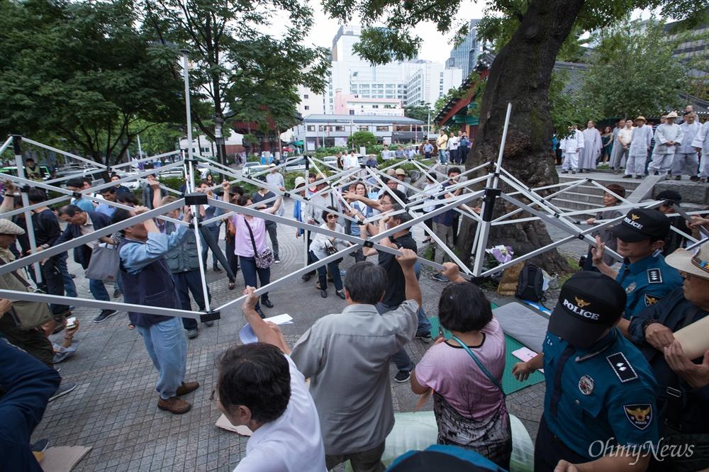 명진스님이 18일 오전 조계사 입구에서 조계사 자승 총무원장 퇴진 촉구 무기한 단식농성을 시작하자 지지자들이 천막을 설치하고 있다.