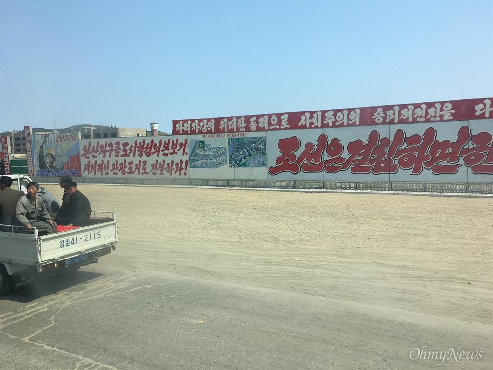 원산 시내 선전 간판 옆을 시민들이 지나가고 있다.