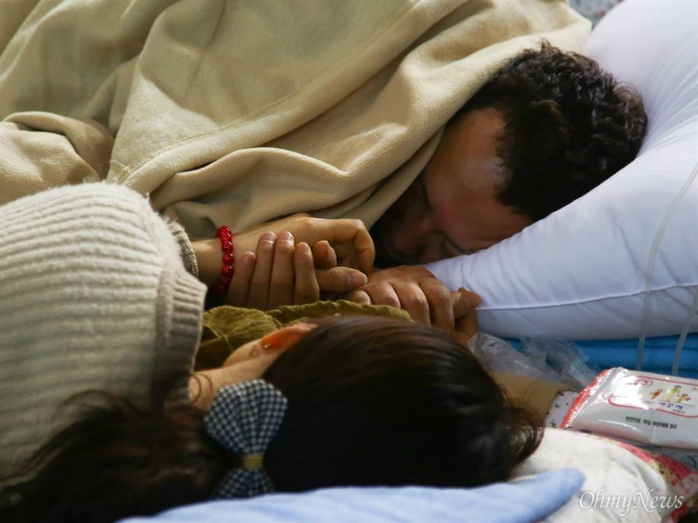 세월호 미수습자 남현철군의 아빠와 엄마가 2014년 4월 17일 진도체육관에서 쓰러져 링거를 맞으며 손을 꼭잡고 있다.