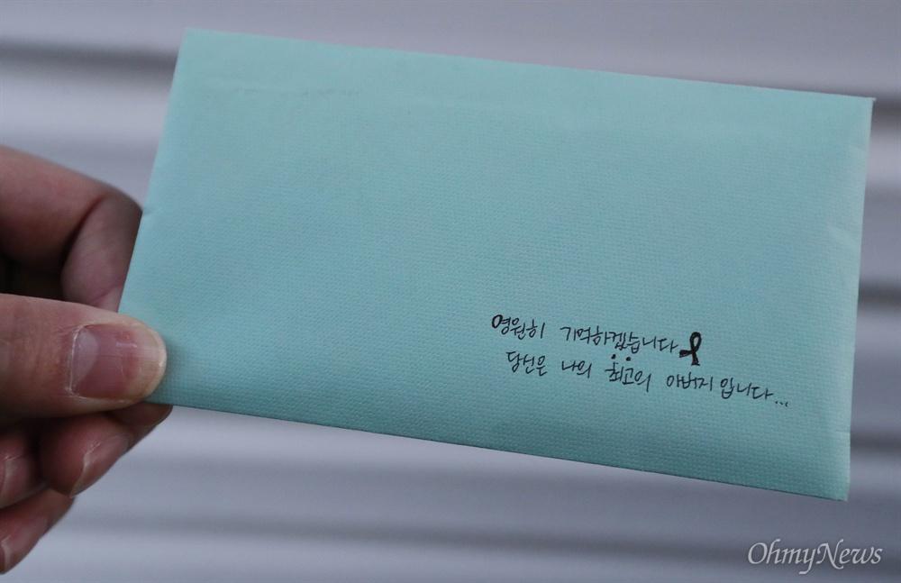 """양승진 선생님, 딸이 보내는 편지 받아주실거죠? 세월호 미수습자 양승진 선생님의 딸이 18일 오전 목포신항 세월호 선체 선수부 인근 안치실에서 '시신 없는' 입관식을 하며 아버지에게 쓴 편지. 봉투 겉면에 """"영원히 기억하겠습니다. 당신은 나의 최고의 아버지입니다.""""라고 적혀 있다."""