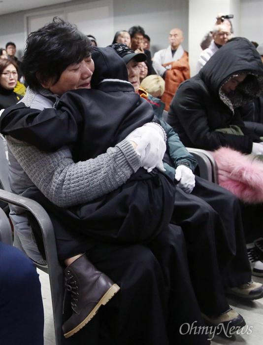 상복 입기엔 너무 어린 아홉살 세월호 미수습자 권재근씨의 딸(9세))이 18일 오전 목포신항에서 열린 세월호 미수습자 합동 추모식에 상복을 입고 참석해 남은 가족들의 품에 안겨 있다.