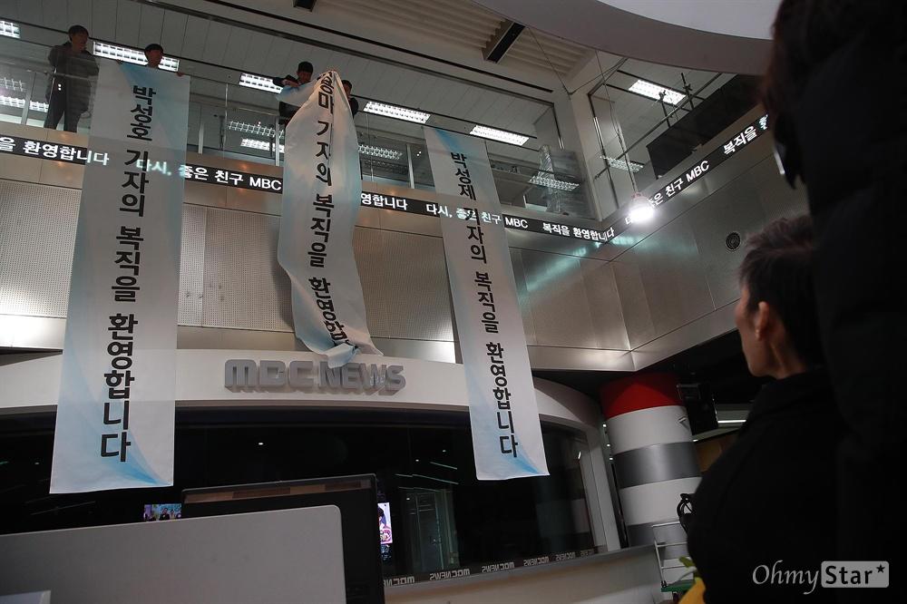 MBC 보도국에 펼쳐진 복직 환영 현수막 지난 2012년 MBC 파업을 이끌었다는 이유로 해고됐다 복직한 이용마 기자가 11일 오전 서울 마포구 MBC 사옥 보도국에 첫 출근하자, 구성원들이 복직을 환영하는 현수막을 펼쳐보이고 있다.