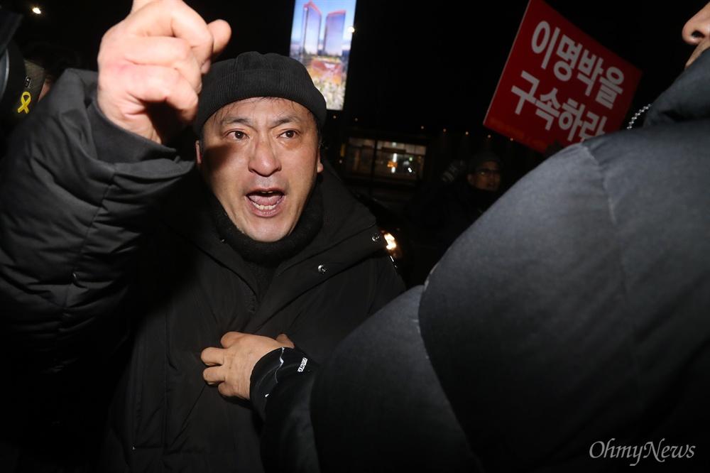 """바깥으로 밀려난 'MB 구속' 시위대 이명박 전 대통령이 트리플데이를 앞두고 18일 오후 서울 강남구 신사동의 한 식당에서 친이계 전·현직 수석 및 의원들과 송년 회동을 위해 도착하자, """"이명박 구속""""을 외치는 시위대가 경호원들에 둘러싸여 식당 바깥으로 밀려나고 있다."""