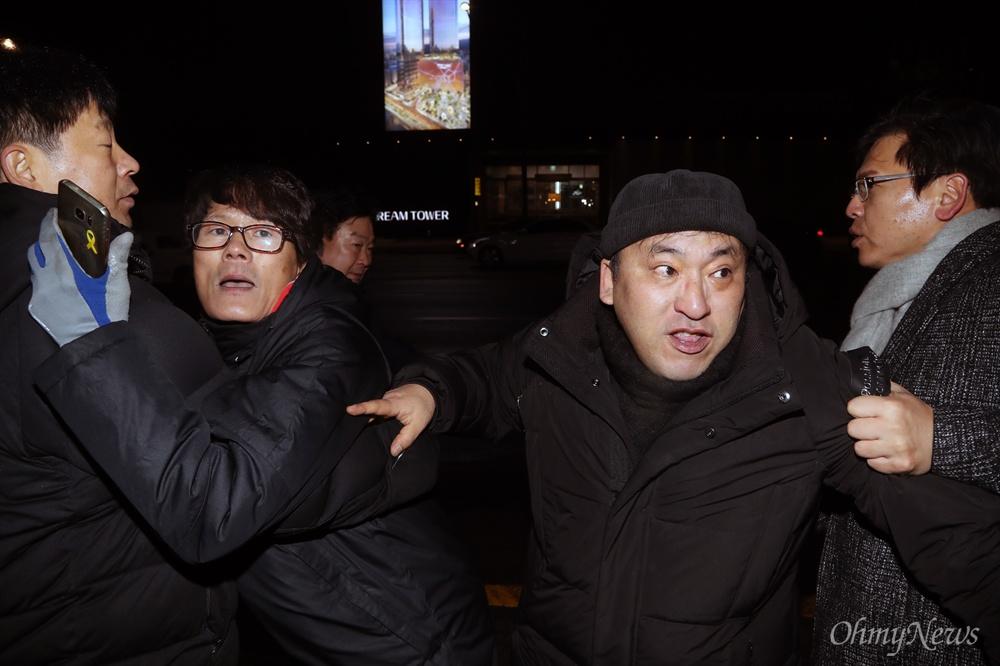 """MB 회동장으로 돌진하는 시위대  이명박 전 대통령이 트리플데이를 앞두고 18일 오후 서울 강남구 신사동의 한 식당에서 친이계 전·현직 수석 및 의원들과 송년 회동을 위해 도착하자, """"이명박 구속""""을 외치는 시위대가 경호원들에 둘러싸여 식당 바깥으로 밀려나고 있다."""