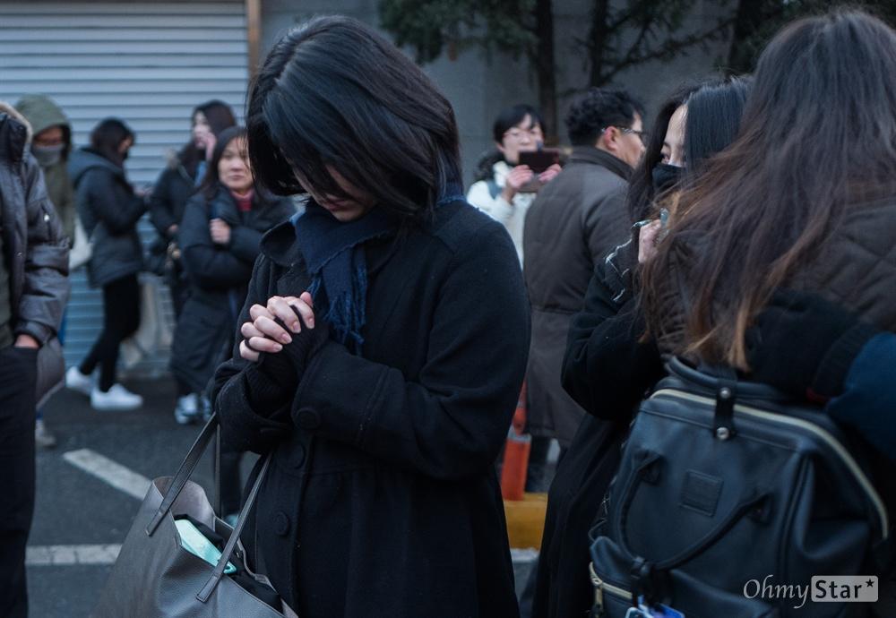 21일 오전 서울 강동구 서울아산병원에서 샤이니 멤버 고 종현의 발인이 끝나자 한 팬이 기도를 하고 있다.