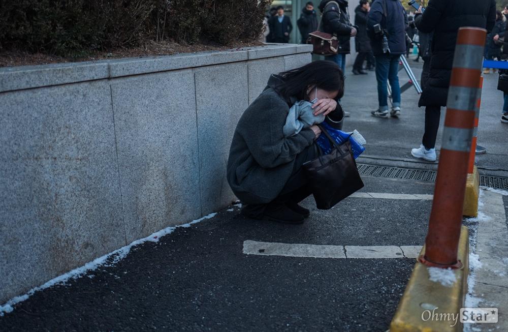 21일 오전 서울 강동구 서울아산병원에서 샤이니 멤버 고 종현의 발인이 끝나자 한 팬이 주저 앉아 울고 있다.