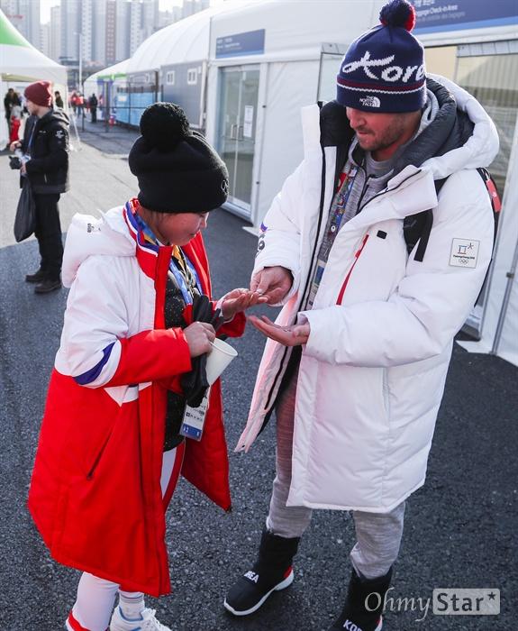 피터 올레닉 남측 국가대표 프리스타일스키 코치와 김련향 북측 알파인스키 선수가 8일 오후 강원도 강릉 올림픽 선수촌에서 기념 배지를 교환하며 즐거워 하고 있다.