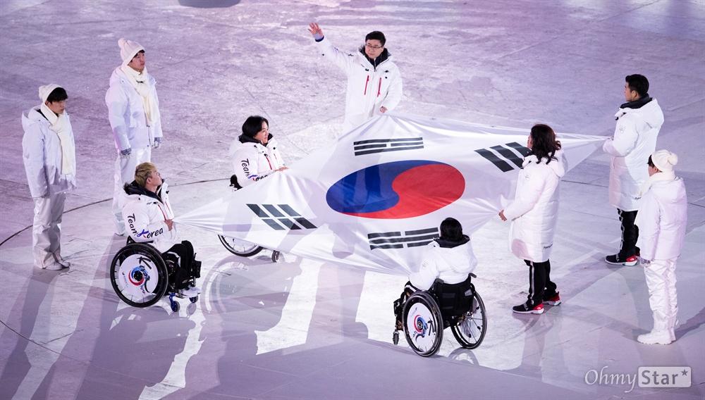 18일 오후 강원도 평창올림픽스타디움에서 열린 2018평창패럴림픽 폐회식에서 방민자(휠체어컬링), 이치원(알파인스키), 박항승(스노보드), 이도연(노르딕스키), 이정민(노르딕스키), 장동신(장애인아이스하키) 선수가 태극기를 들고 입장하고 있다.