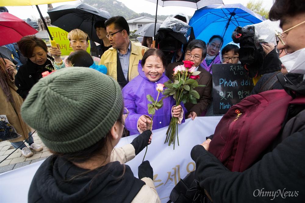 한배평화재단 회원들과 베트남전 한국군 민간인학살 피해자 웅우예티탄씨가 23일 오전 서울 종로구 청와대 앞 분수대에서 베트남전 종전 43주년 기념 기자회견을 열고 민간인학살 진상규명과 사과를 촉구 하고 있다. 기자회견 참가자들이 웅우예티탄씨에게 '사과의 꽃'을 전달하고 있다.