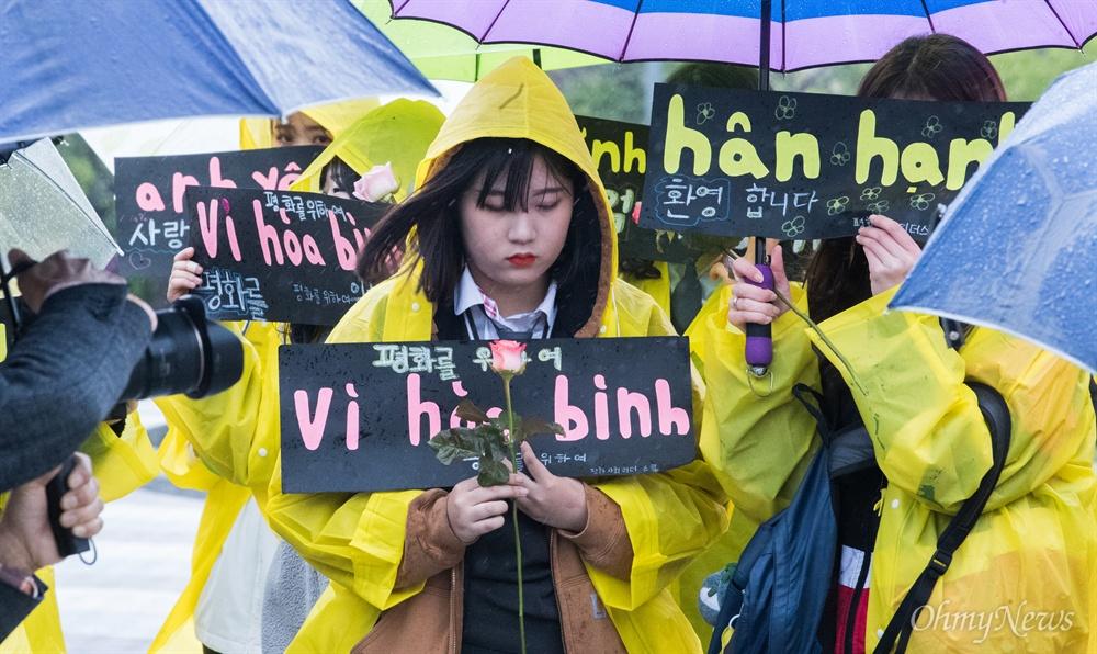 한배평화재단 회원들과 베트남전 한국군 민간인학살 피해자 웅우예티탄씨가 23일 오전 서울 종로구 청와대 앞 분수대에서 베트남전 종전 43주년 기념 기자회견을 열고 민간인학살 진상규명과 사과를 촉구 하는 동안 한 학생이 '평화를 위하여'가 적힌 손피켓과 장미꽃을 들고 함께 하고 있다.