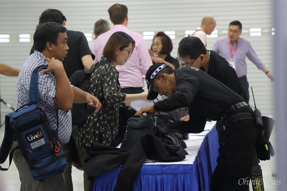 소지품 검색 받는 취재기자들 사상 첫 북미정상회담을 이틀 앞둔 10일 오전 싱가포르 마리나베이 포뮬러원(F1) 경기장 건물에 마련된 미디어센터에서 경호원들이 외부인의 출입을 통제하며 소지품을 검사하고 있다.