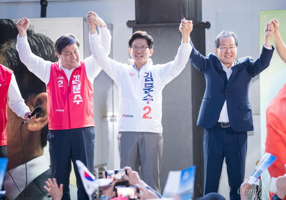 자유한국당 홍준표 대표가 선거를 하루 앞둔 12일 오후 서울 중구 대한문 앞에서 김문수 서울시장 후보 유세에서 후보자와 함께 손을 들어 올리고 있다.