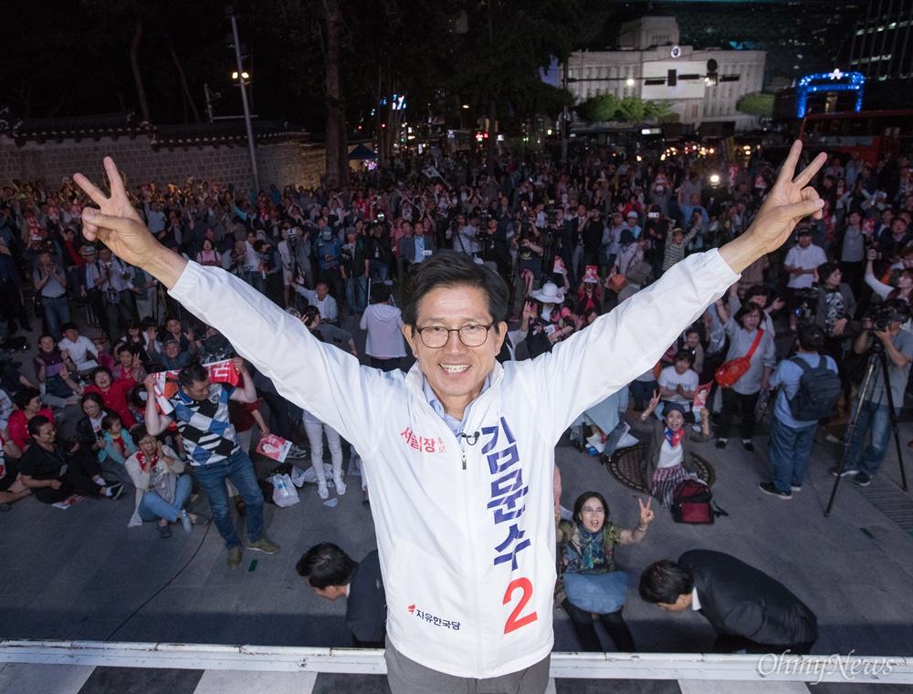 자유한국당 김문수 서울시장 후보가 12일 오후 서울 중구 대한문 앞에서 열린 유세에서 브이를 한 팔을 들어 올리고 있다. 뒷쪽에는 서울시청사가 보이고 있다.