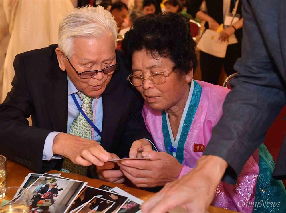20일 금강산호텔에서 열린 제21차 남북 이산가족 단체상봉 행사에서 남측 유관식(89) 할아버지가 딸 유연옥(67)과 사진을 보고 있다.