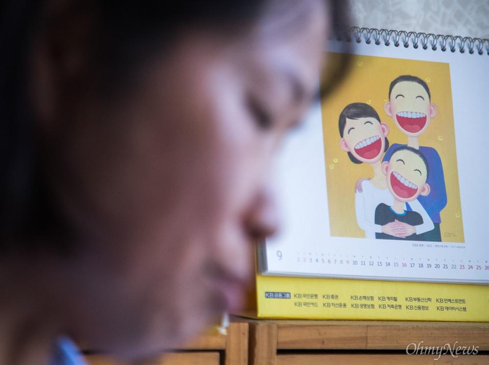 """군피해자 고 조성현 일병의 어머니 이근옥씨는 """"달력에 있는 그림이 자신의 두 아들과 행복했을 때 모습 같아 보인다""""며 과거를 회상 했다."""