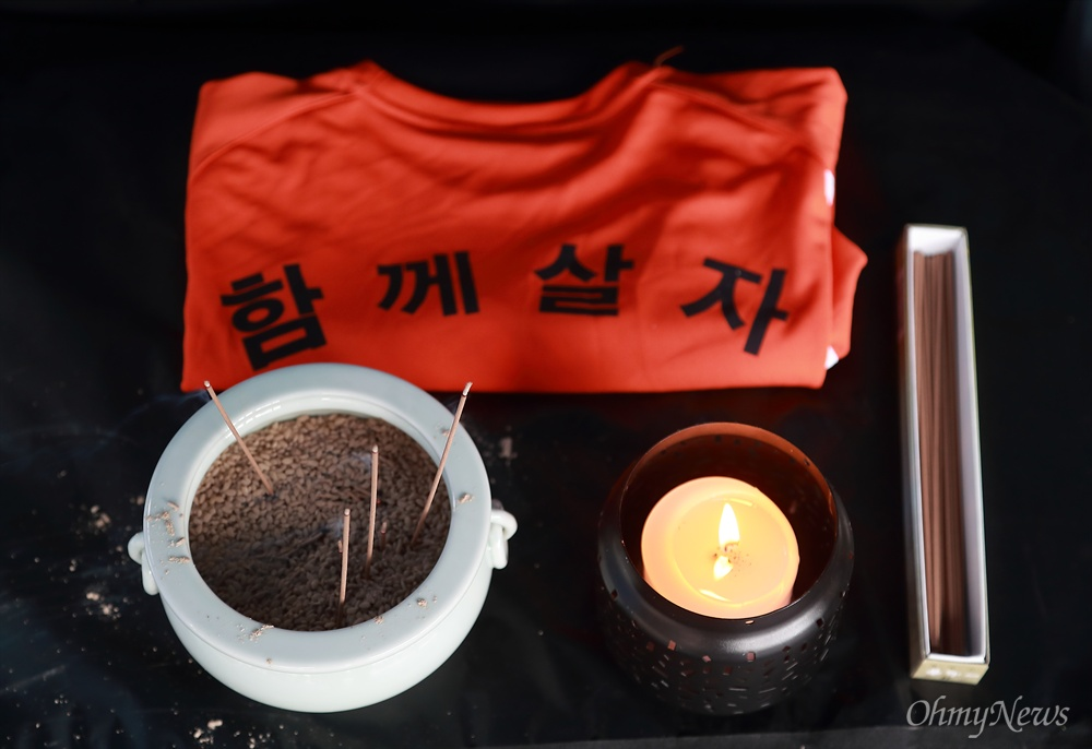 쌍용차 해고노동자 복직 잠정 합의안이 발표된 14일 오전 서울 덕수궁 대한문앞 희생자 합동분향소에 '함께살자' 티셔츠가 놓여 있다.