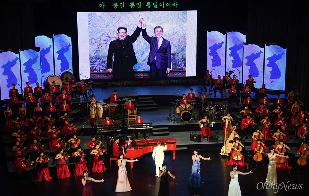 18일 오후 평양대극장에서 남북 정상이 참석해 열린 삼지연 관현악단의 환영공연에서 예술 단원들이 판문점 선언 당시 사진을 배경으로 공연하고 있다.