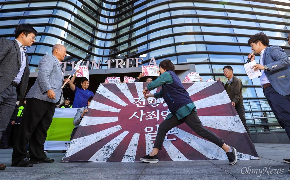 전쟁반대평화실현국민행동 활동가들이 1일 오후 서울 종로 일본대사관 앞에서 10일 열리는 '제주 국제관함식'에 욱일기를 달고 오겠다는 일본을 규탄하며 욱일기를 베는 퍼포먼스를 하고 있다.
