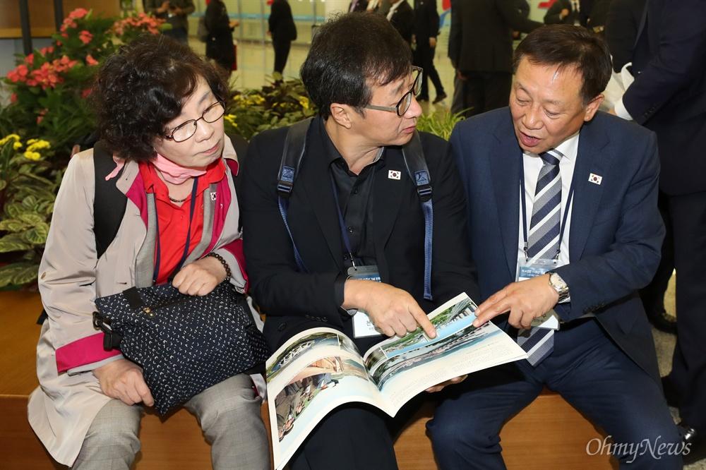 '10.4 선언 11주년 기념 민족통일대회' 참석자들이 4일 오전 평양 순안국제공항에 도착해 북측 안내책자를 살펴보고 있다.
