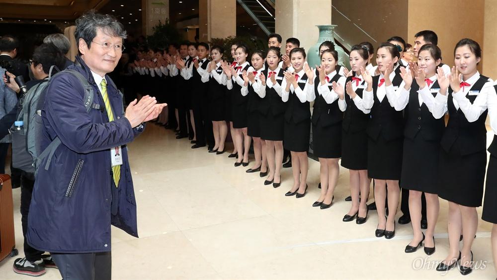 4일 오전 평양 고려호텔에서 '10.4 선언 11주년 기념 민족통일대회' 참석차 방북한 문성근 노무현 재단 이사가 환영하는 북측 봉사원들을 바라보며 박수치고 있다.